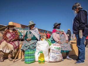 Un representante del Programa Mundial de Alimentos en Bolivia habla con una mujer indígena Uru-Murato sobre el COVID-19 y la buena nutrición.