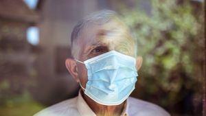 Hombre mayor mirando por la ventana. Coronavirus, Covid-19.