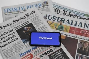 Ilustración muestra una pantalla de teléfono con el logotipo de Facebook y los periódicos australianos en la Casa del Parlamento en Canberra, Australia, 18 de febrero de 2021.