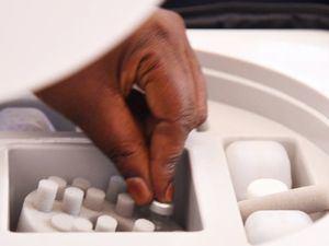Un trabajador sanitario recoge un vial de la vacuna COVID-19 de AstraZeneca de un recipiente refrigerado en Uganda.