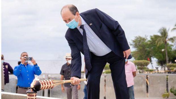 Embajador Biran encendiendo una antorcha.