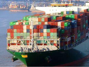 Barco contenedor descargando en un puerto.