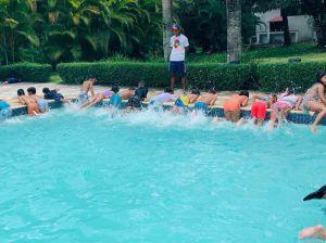 Niños ejercitándose en la piscina junto a entrenador.