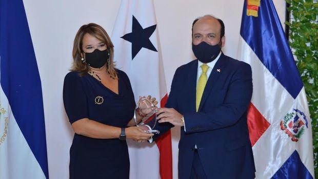 El viceministro de MICM Ramón Perez entregó una placa a Isabel Estévez.