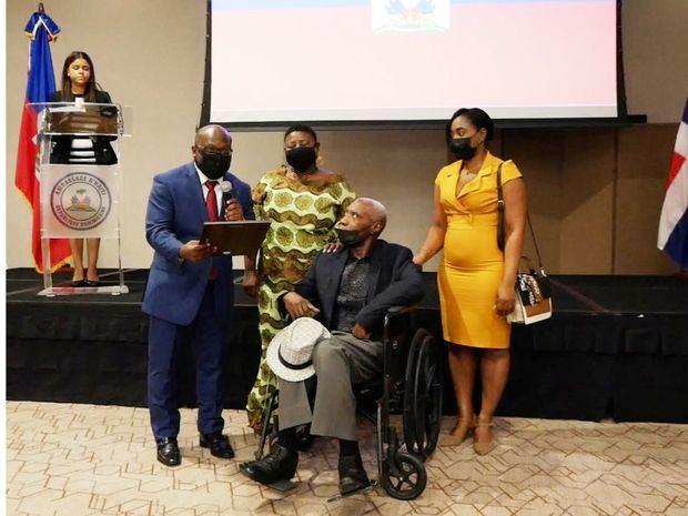 Embajador Smith Augustin entrega placa de reconocimiento al artista haitiano Cédon.