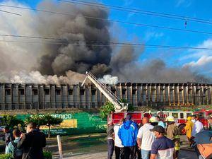 Bomberos sofocan el incendio en el almacén.