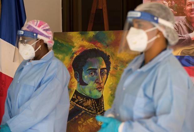 Dos funcionarias de Salud Pública esperan junto a una imagen de Simón Bolívar en la embajada venezolana, donde decenas de ciudadanos de ese país acudieron a realizarse pruebas PCR, este lunes en Santo Domingo.