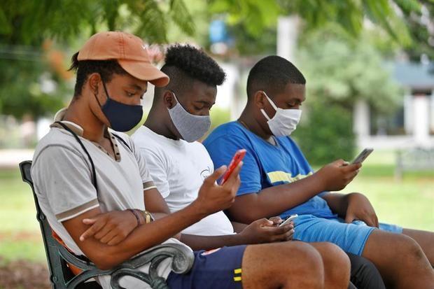 Jóvenes observan sus teléfonos, en una zona wifi, en La Habana, Cuba.