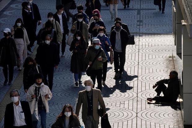 Los peatones pasan junto a una persona sin hogar (d) sentada con una lata en el distrito de negocios de Shinjuku en Tokio, Japón.