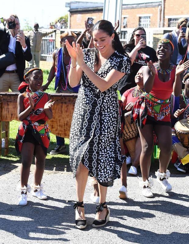 La duquesa de Sussex durante un viaje a Sudafrica lució un vestido estampado en negro y blanco con línea 'wrap'.
