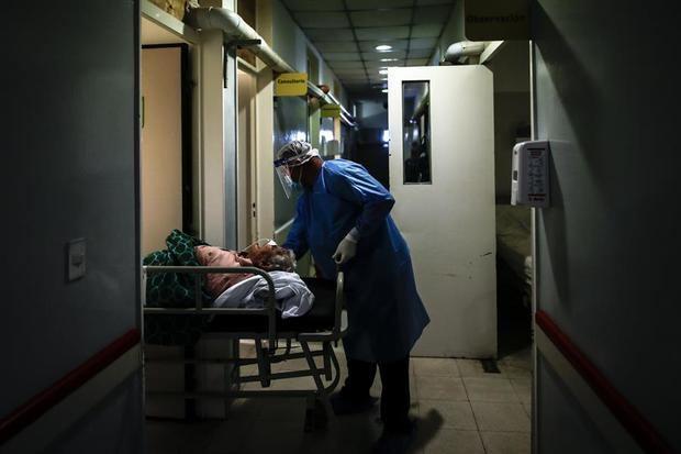 Un camillero realiza el traslado de una mujer con covid-19 en una unidad de terapia intensiva en un hospital de la Provincia de Buenos Aires.