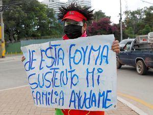 Una mujer vestida de payaso pide ayuda económica en una calle de Tegucigalpa, Honduras.