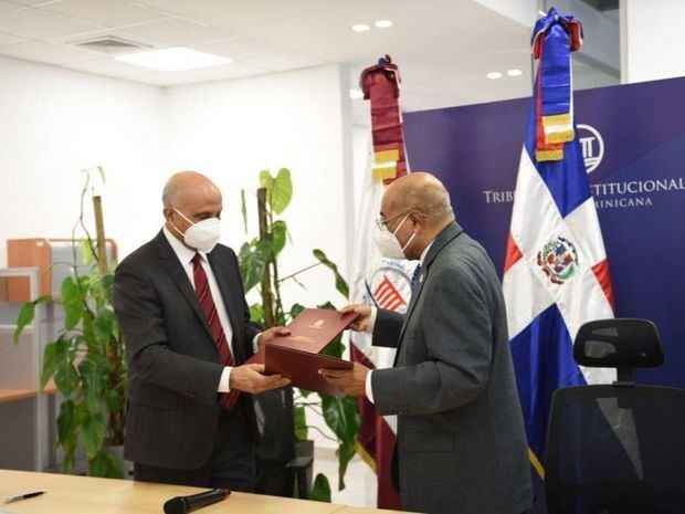 Juan José Disla Ledesma y Miltón Ray Guevara, intercambian el acuerdo.