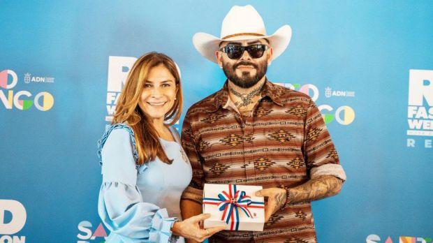 La alcaldesa Carolina Mejía entrega un regalo al estilista Antonio Esteban.