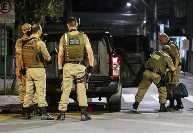 Miembros de la policía recogen el dinero que los asaltantes dejaron en la madrugada de este martes, en una de las calles en Criciuma. Miembros de la policía recogen el dinero que los asaltantes dejaron en la madrugada de este martes, en una de las calles en Criciuma.