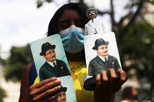 Una mujer sostiene hoy imágenes de José Gregorio Hernández con motivo de su ceremonia de beatificación, frente a la iglesia de Nuestra Señora de la Candelaria, en Caracas, Venezuela.