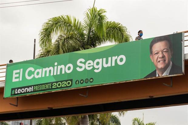 Una mujer con tapabocas es vista mientras pasa cerca a una valla publicitaria del candidato presidencial Leonel Fernández, este sábado en Santo Domingo.