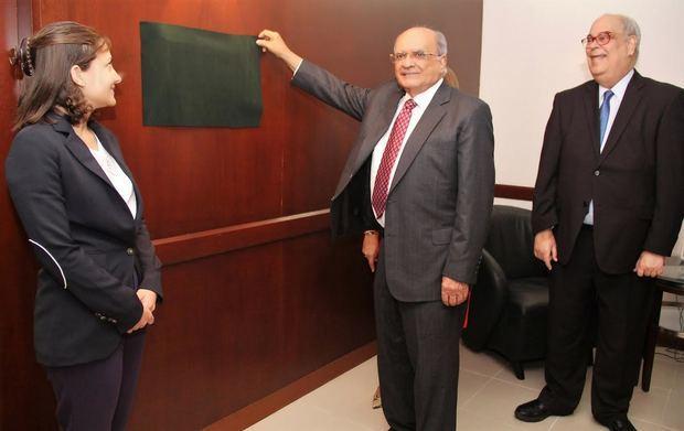 El empresario Andrés Avelino Abreu develiza el letrero que designa con su nombre el salón de conferencias de Acofave. Le acompañan, Carla Frías y Enrique Fernández.