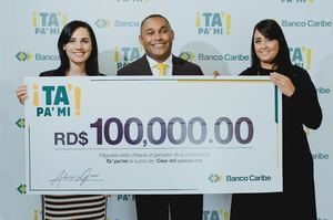 Xiomy Ramírez y Claudia Alcántara, de Banco Caribe, entregan el premio a David Colón.