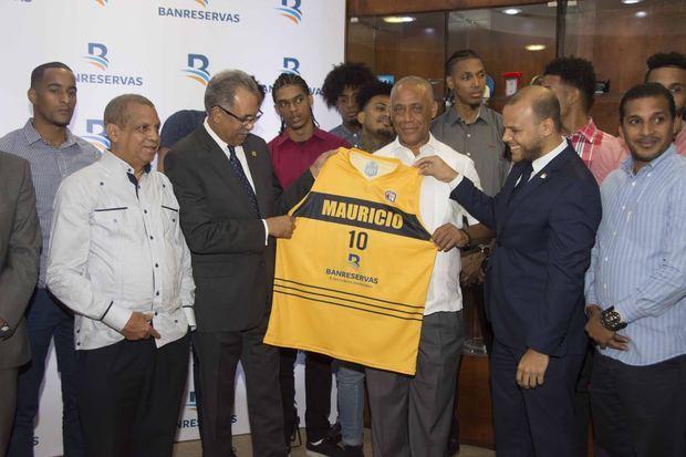 Leo Corporán y José Boyón Domínguez entregan camisetas del equipo al administrador general de Banreservas, Simón Lizardo Mézquita.