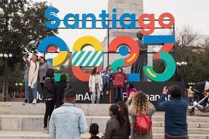 Un grupo de personas se toma fotografías este sábado frente a un cartel que anuncia la celebración de los juegos Panamericanos y Parapanamericanos 2023, en Santiago (Chile) durante el lanzamiento oficial de la capital como sede.