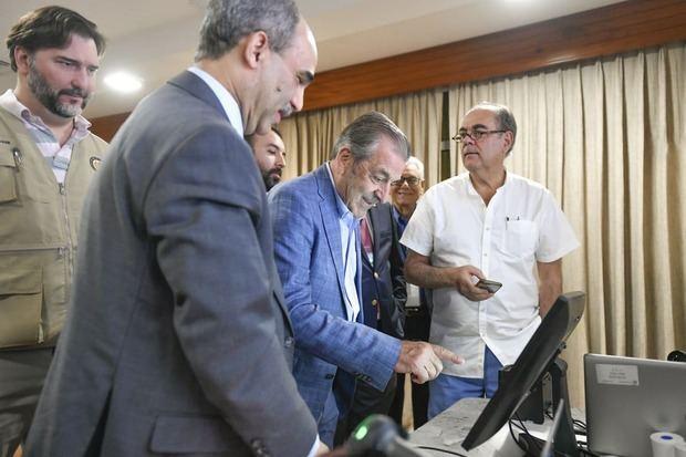 Observadores de la OEA mientras veían modelo del voto automatizado.