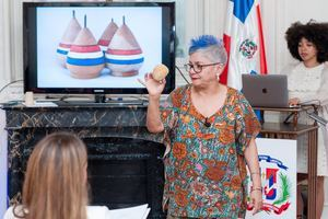 Xiomarita Pérez mostrando un trompo artesanal, durante conferencia 'A brincar la tablita con Xiomarita'.