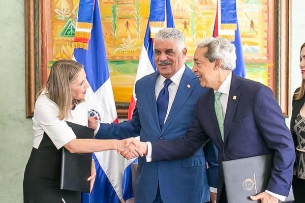 El presidente de Adoexpo, Luis Concepción y la decana del CC, Clara Reid, se saludan luego de firmar el acuerdo. Observa, el canciller Miguel Vargas.