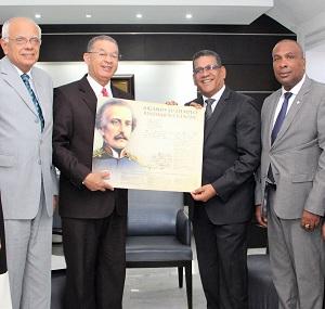 Wilson Gómez, Manuel Rodríguez y Víctor Zalaba entregan símbolos patrios a Rubén Maldonado.