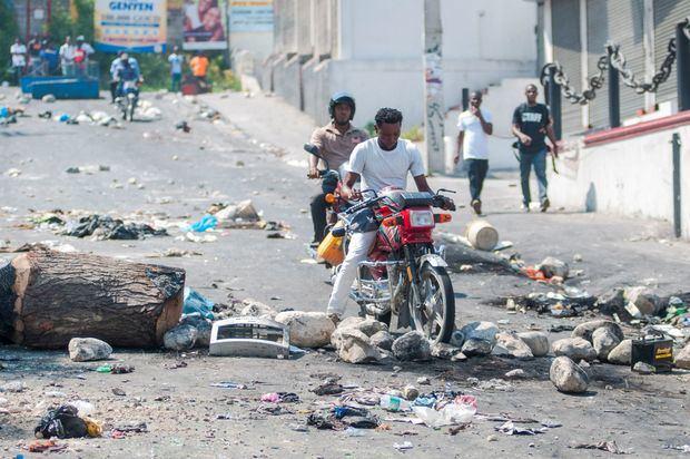 Personas en motocicleta pasan por una vía bloqueada con escombros durante una protesta este lunes, en Puerto Príncipe (Haití). Puerto Príncipe y otras ciudades de Haití se paralizaron en una nueva jornada de protestas por la escasez de combustible, que se prolonga desde el pasado agosto.