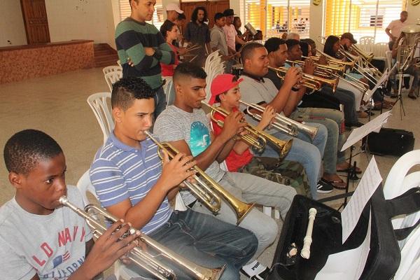 En primer plano, el maestro Samuel Ureña Gonzáles acompaña a los jóvenes en su práctica de trompeta, donde se evidencia la concentración y la entrega de cada uno. En el fondo, un grupo de trombones, tuba y percusión en la misma armonía de los ejercicios.