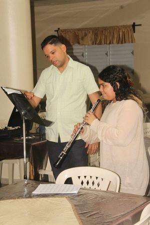 Hardy Balbino Núñez Concepción, profesor de la Orquesta Sinfónica Nacional, instruye a la joven estudiante de oboe en la técnica de respiración.