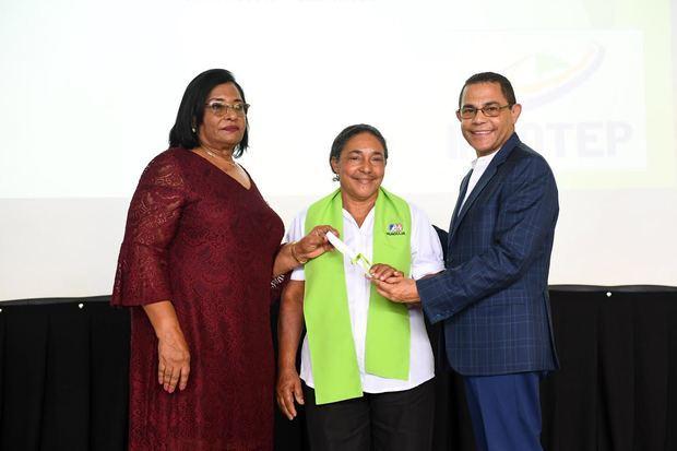 Rafael Ovalles y Luisa Ramírez entregan certificados a egresadas a los programas de emprendimiento, costura industrial y manualidades.