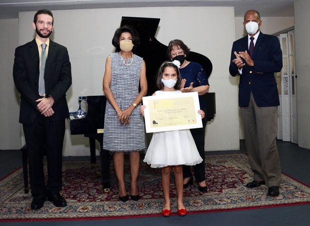 La niña Vega Marrero, recibe su certificado de manos de los organizadores del evento.