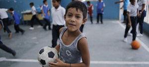 Un niño juega al fútbol en la escuela El Carmen en Petare, Caracas, Venezuela.