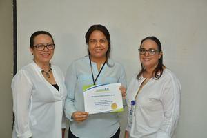 Odalis Rojas de Link Gerencial junto a Reyna Alburquerque entregan diploma a Iris Romano.