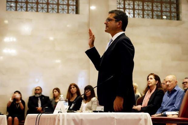 El abogado Pedro Pierluisi levanta su mano derecha durante una vista pública en la Cámara este viernes en San Juan, Puerto Rico, asumiendo así el cargo de nuevo gobernador.
