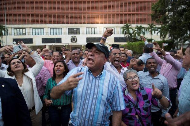 Manifestantes participan durante una protesta en contra de una posible reforma a la Constitución que permitirá la reelección del Presidente Danilo Medina, el enfrentamiento tuvo lugar frente al Congreso Nacional de la República Dominicana.