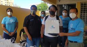 Juan Miguel Fox (al centro) recibe su kit por parte de la directiva.