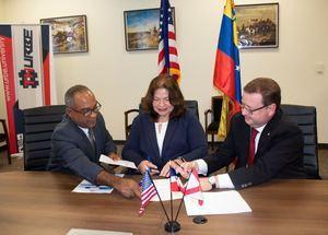 Desde la izquierda, Olivo De León, Marry Carrillo y Armando Salas intercambian los documentos de convenio.