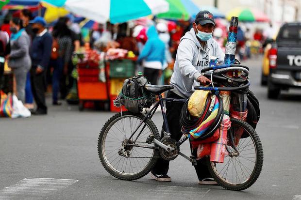 Un hombre empuja una bicicleta hoy en una calle cercana al mercado de Riobamba, Ecuador.