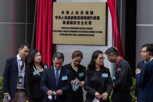 Los invitados pasan la señal de la Oficina de Protección de la Seguridad Nacional de Pekín en Causeway Bay, Hong Kong, China.