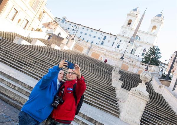 Una pareja se hace un selfi ante la escalinata de la Plaza de España en Roma.