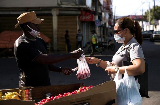 Un haitiano fue registrado al venderle una bolsa de cerezas a una mujer, durante el estado de emergencia para combatir la pandemia del virus COVID-19, en el barrio Pequeño Haití de Santo Domingo, Rep. Dominicana.