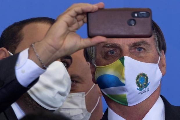 El presidente de Brasil, Jair Bolsonaro (d), fue registrado el pasado martes al tomarse una fotografía, durante un evento oficial en Brasilia, Brasil.