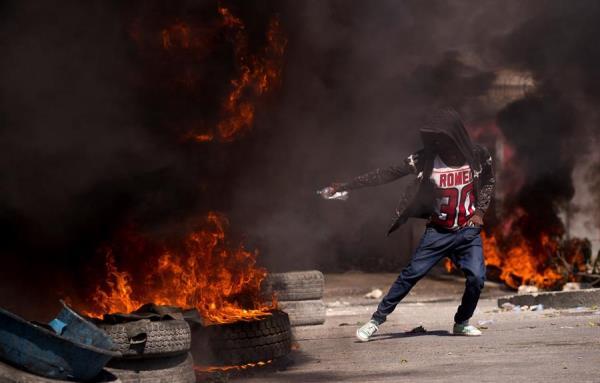 Un manifestante aviva el fuego de una barricada de llantas en llamas en la zona próxima al aeropuerto internacional de Puerto Príncipe (Haití).