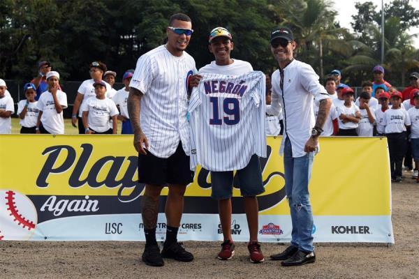 Marc Anthony (d) y el pelotero de los Chicago Cubs, Javier Báez (i), posan junto al pelotero de Little Leagues de Puerto Rico Owen Negrón (c), en la ceremonia de inauguración de un campo de béisbol recientemente renovado, hoy sábado en Loíza. Anthony y Báez celebraron este sábado la reconstrucción de un campo de béisbol en la localidad puertorriqueña de Loíza, que fue destruido por los huracanes Irma y María en 2017.
