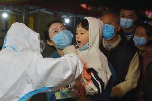 Un trabajador médico toma una muestra de hisopo de un niño residente para la nueva prueba de coronavirus en un bloque residencial en la ciudad de Qingdao, provincia de Shandong, China.