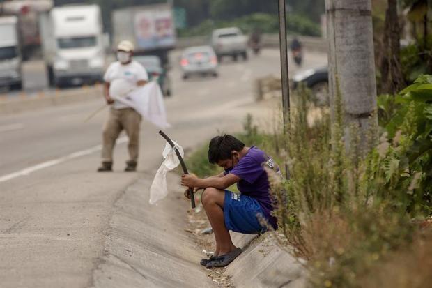 Un niño ondea una bandera blanca en la carretera pidiendo ayuda por hambre debido a la crisis economica provocada por el coronavirus, el 29 de abril de 2020, en El Tejar, Guatemala.