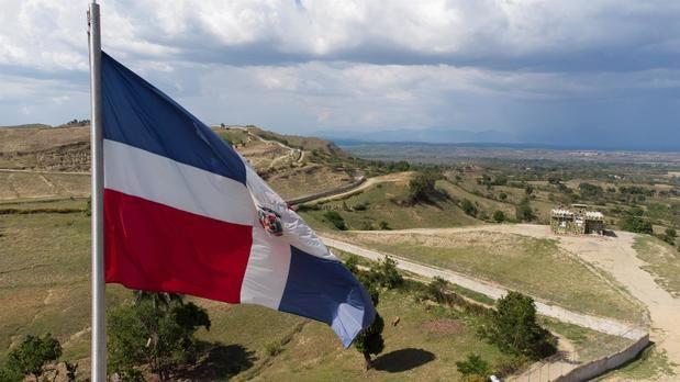 Fotografía aérea tomada con un dron que muestra la bandera de República Dominicana mientras ondea sobre la verja fronteriza entre República Dominicana y Haití, el 8 de mayo de 2021, en Comendador, colinas de Elías Piña, República Dominicana.